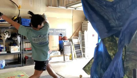 Marco Torres, senior, does batting practice in his garage.