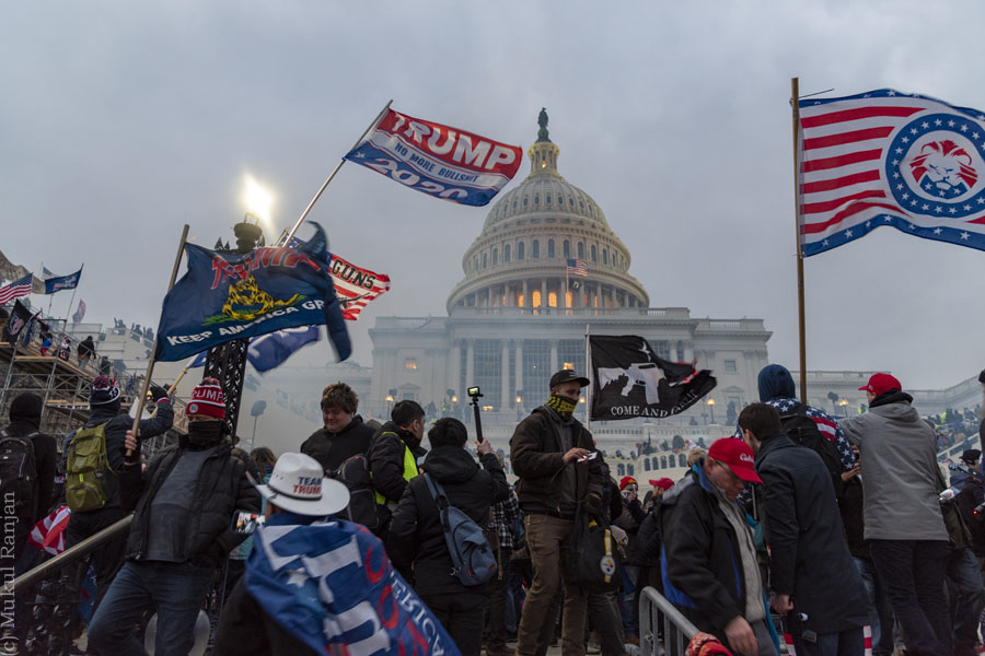 The pro-Trump mob stand outside the Capitol.