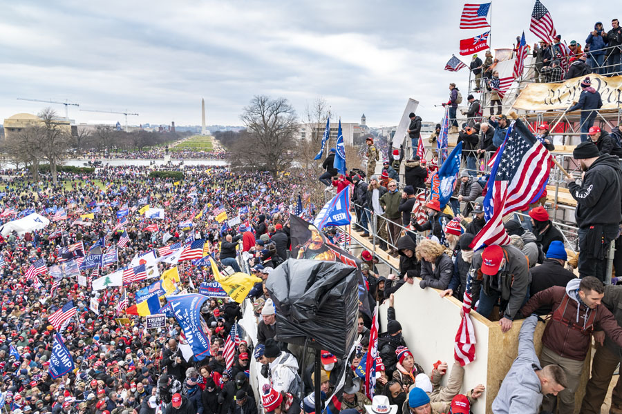 The maskless mob gathers with Trump flags in hand.