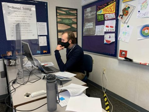English teacher Scott Von Essen navigates several screens so he can have his lesson pulled up while also being able to see the students at home.