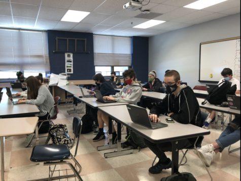 Students, spaced 3 feet apart, work on their Chromebooks