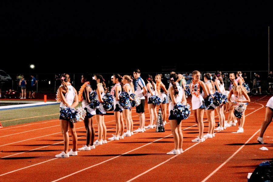 North cheerleaders stand on the sidelines of the football field