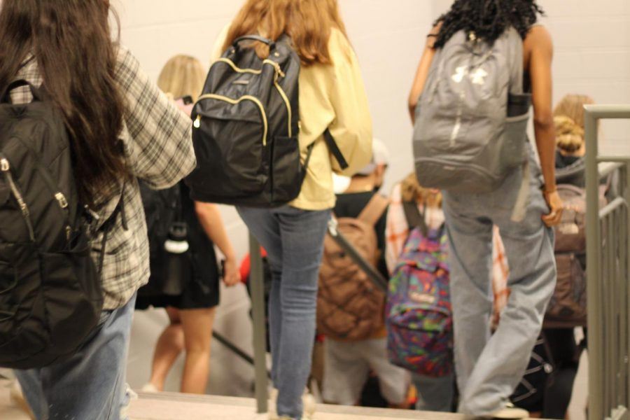 Students walk down the one-way staircase inconveniently located in the middle of a hallway.
