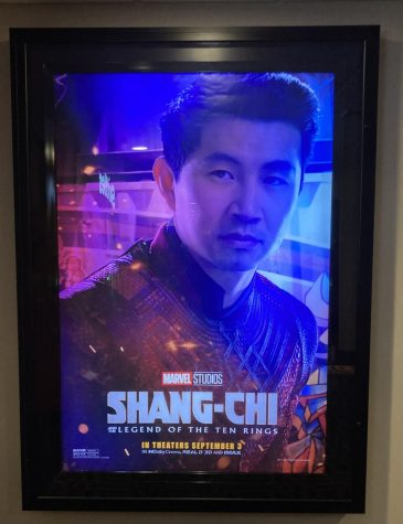 A promotional poster for Shang-Chi and the Legend of the Ten Rings hangs outside a movie theater.
